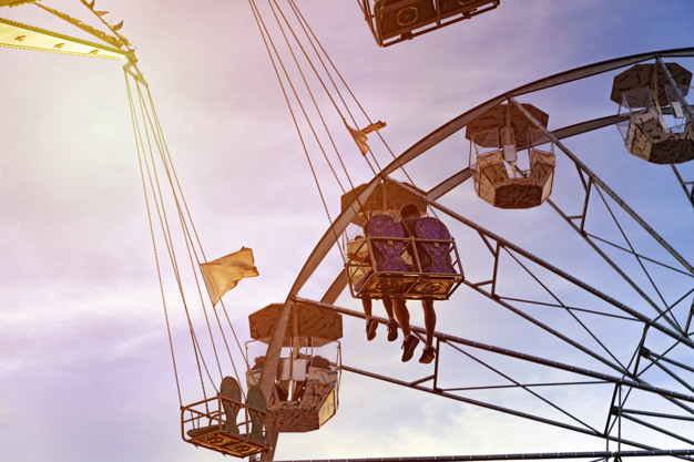 fun in the lunapark, people on the rollercoaster and big wheel,